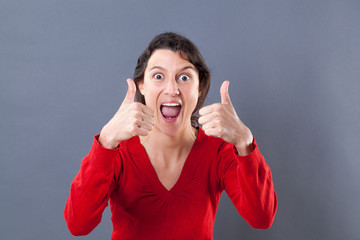 optimism concept - ecstatic beautiful young woman shouting with two thumbs up for excitement and success, studio grey background