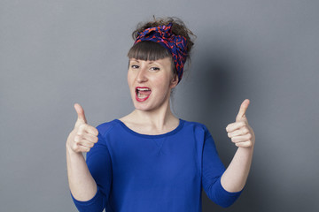 optimism concept - impressed retro 30s woman laughing with two thumbs up for exciting success, studio grey background