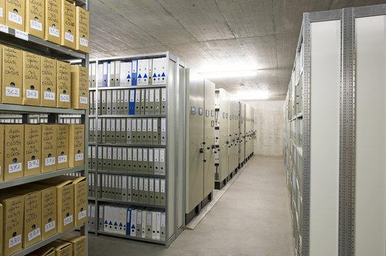Archiv einer Firma mit Regalen voller Aktenordner.