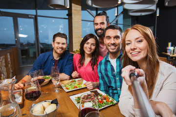 friends picturing by selfie stick at restaurant