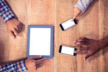 Cropped image of hands using mobile phone and tablet PC