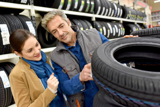 Customer in car shop choosing new tires with help of seller