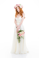 Smiling redhead woman in dress holding flowers