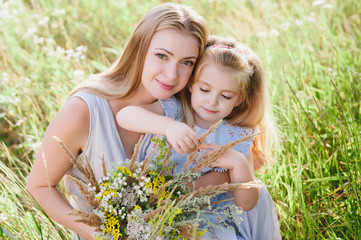 Mom and daughter in nature with a bouquet of wild flowers, family, family values, childhood, lifestyle