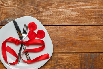 The red ribbon in plate on wooden background