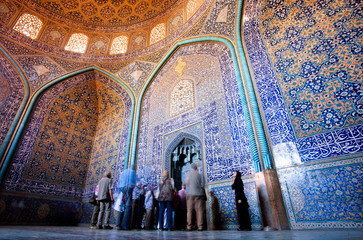 Group of tourists view beautiful interior design of patterned Lotfollah Mosque in Isfahan