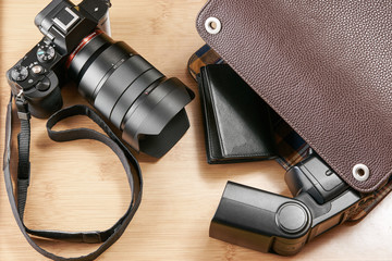 Shot of a mirror-less camera and flash unit on a wooden surface