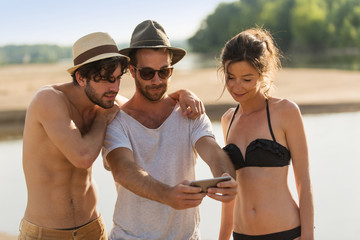 In Summer, three friends taking selfies at the beach during the holidays