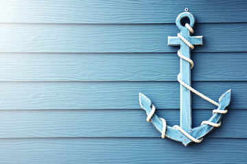 Anchor on blue wooden background.