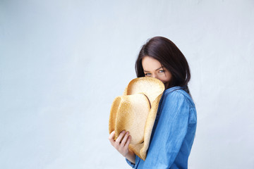 Smiling woman covering face with cowboy hat