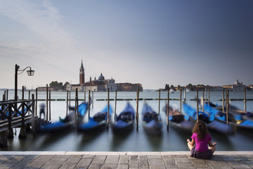 Woman meditating in venice with blue boats in background