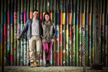 Happy young couple standing in front of the colorful wooden wall