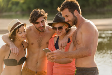 At the beach, four friends are looking selfies at a smartphone
