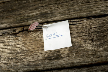 White piece of paper with the word Goal pinned to a rustic woode
