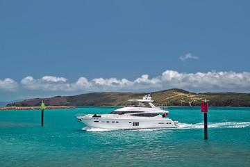 A luxury cruiser navigates through channel markers to enter the Hamilton Island marina, Australia.