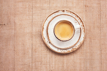 Cup of coffee on burlap background. Top view, toned,  copy space