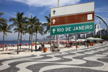 Sign on sidewalk next to the beach in Rio de Janeiro
