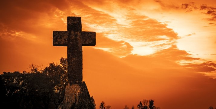 Stone Cross Background. Stone crucifix set against a dramatic red sky background.