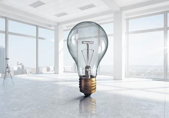 Glowing light bulb in modern office