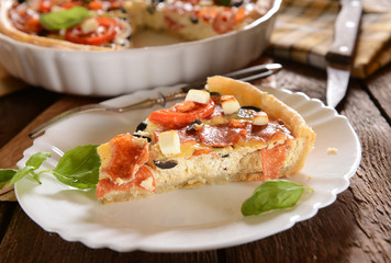Tart (Quiche) with tomatoes, basil, salami, black olives and che