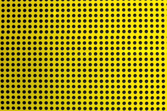 Yellow metal texture of holes over a black background (selective