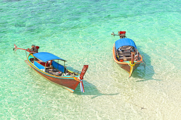 Two boats floating on a shallow water, tropical holidays concept.