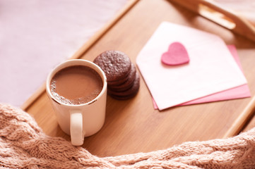 Cup of coffee with chocolate cookies, envelopes with heart, knitted cloth on wooden tray. Celebrating Valentines day. Romance.