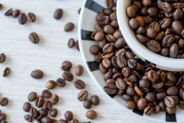 Detail view of coffee cup filled with coffee beans on white table. Selective focus.