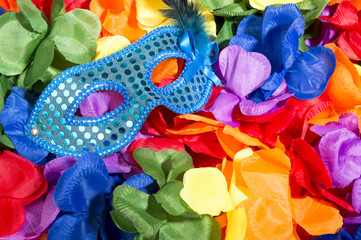 Sparkly carnival mask sitting on brightly colored background of flower leis