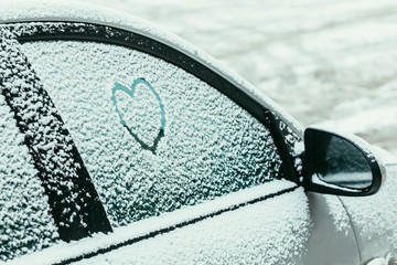 Heart drawn on a car windshield covered with fresh snow