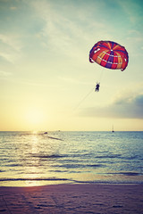 Retro stylized paragliders at sunset, summer adventure concept.