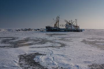 old trawler frozen in the ice