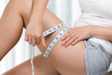 メジャーで太ももを測る女性