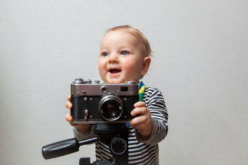 One year old boy with vintage old time photo camera