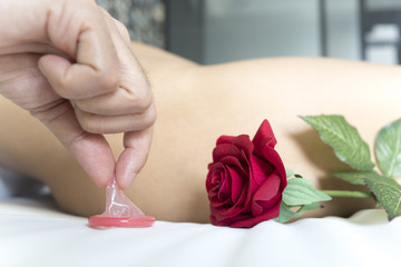 Condom and red rose on bed with woman on background