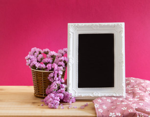 White vintage photo frame with sweet statice flower in basket