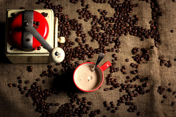 coffee grinder with a cup of coffee and beans, top view
