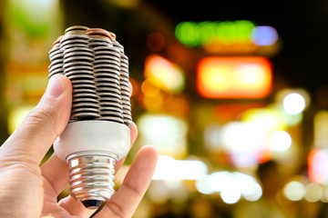 hand holding coin light bulb with defocused city night light background, energy concept