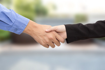 Business man and woman handshake on blur background