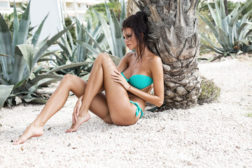 Sexy model in swimsuit resting under the palm