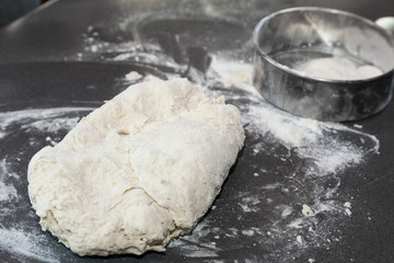 piece of fresh dough with blurred flour strainer