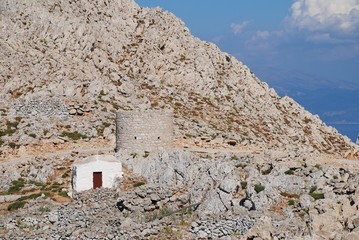 A small chapel and an old stone windmill in the rocky hills above Chorio on the Greek island of Halki.