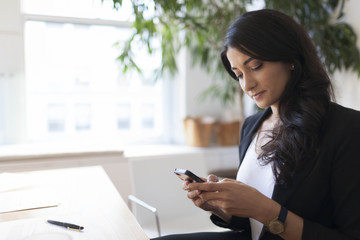 Young businesswoman using smart phone while working in office