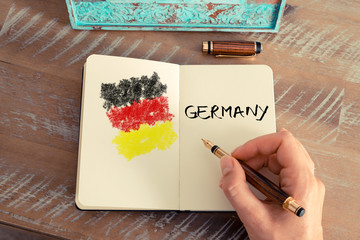 Woman hand drawing Germany flag on notebook