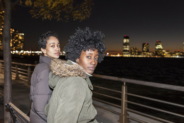 Portrait of two young women sitting by the river at night