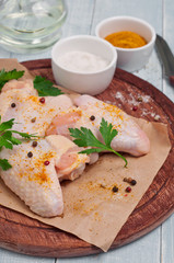 raw chicken wings with curry seasoning, parsley and pepper
