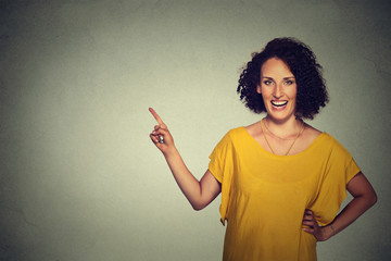 Portrait of attractive middle aged woman pointing at blank gray wall background