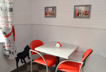 Little table and red chairs in modern cafe. Interior