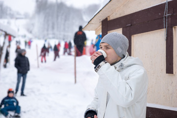 Young man drinking coffee at a ski resort