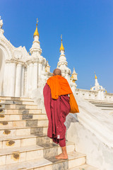 Southeast Asian young Buddhist monks walking morning alms in Inl